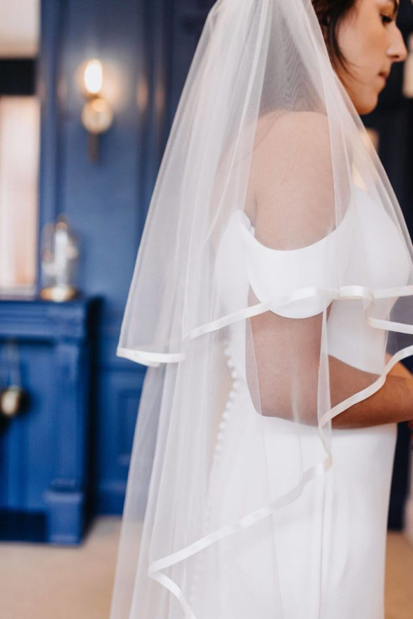 The Hattie is a 2 Tier Veil in classic tulle, decorated all the way around with a 10mm flat ribbon. Click to shop now.